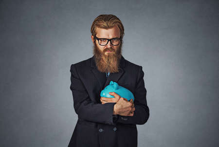 Young formal man in glasses extremely fascinated with money saving holding with greedy hand gesture the piggy bank. Bearded hipster businessman. Isolated on gray studio wall Background. Negative face.