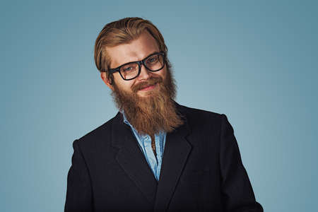 Portrait of handsome Bearded hipster businessman wearing glasses smiling happy Isolated on blue Background. Positive face expression, human emotion, body language, reaction, attitude. Studio shot