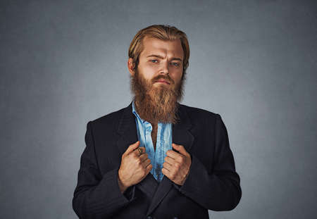 Confident bearded hipster businessman standing looking straight at you with his arms holding black suit jacket Isolated on gray grey studio wall Background. Positive face expression, human emotion. Banco de Imagens