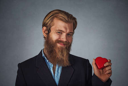 Young happy Caucasian bearded hipster businessman holding red heart shaped gift box ready for Valentine's day. Isolated on gray grey studio wall Background. Negative face expression, human emotion.