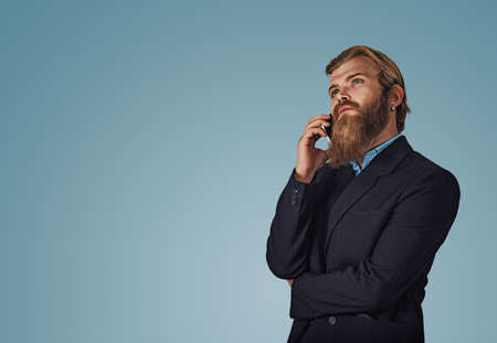 Bearded pensive hipster young businessman male holding cellphone looking up talking speak on phone thinking Isolated on blue Background. Serious face expression human emotion body language reaction