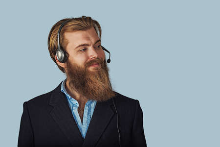 Bearded hipster businessman. Friendly customer service guy over light blue with clipping path Positive face expression, human emotion, body language, reaction, attitude. Studio horizontal shot.