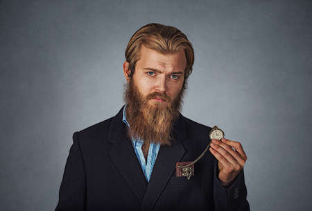 Time is ticking. Bearded hipster serious business man holding showing pocket watch Isolated on gray grey studio wall Background. Negative face expression, human emotion, body language, reaction. Banco de Imagens