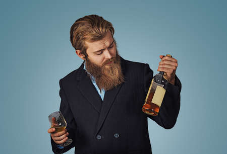 Nice choice. Man holds looks at bottle of cognac whiskey alcohol drink. Social and cultural aspects of drinking. Man thoughtful estimating bottle alcohol. Businessman in formal suit on blue background