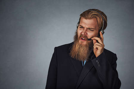 Annoyed customer service employee someone shouting at him on the other side of the line moving the headphone away of his ear isolated on a gray grey background. Bearded hipster business man. Negative