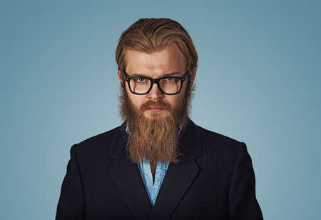 Close up Serious Young Bearded Hipster Businessman Wearing Eyeglasses, Looking at the Camera Against Gray Wall Background with Copy Space. Negative face expression human emotion body language reaction