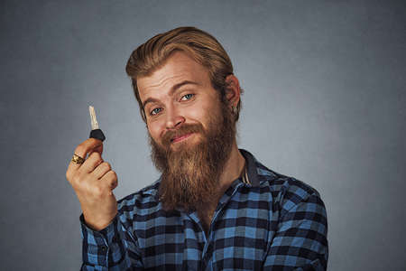 Bearded business man, young handsome man holding car key or new apartment Isolated on gray grey studio wall Background. Positive face expression, human emotion, body language, reaction, attitude