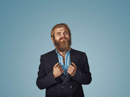 Bearded hipster business man hands on suit showing super hero shirt rising his head looking up and smiling Isolated on blue Background. Negative face expression, human emotion, body language, reaction Banco de Imagens