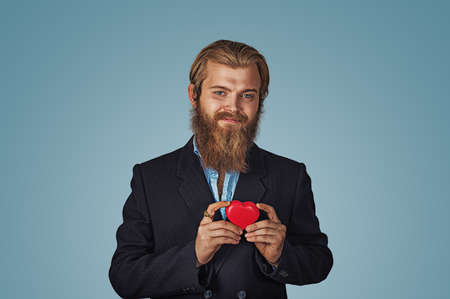 Handsome funny happy businessman in black jacket and blue shirt standing and holding red big heart shaped gift box looking at camera with good feelings. Indoor, studio shot isolated on blue background