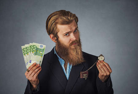 Time is money concept. Handsome Bearded hipster businessman serious skeptical man in blue shirt with cash currency and retro pocket watch Isolated on gray Background. Negative face expression emotion.
