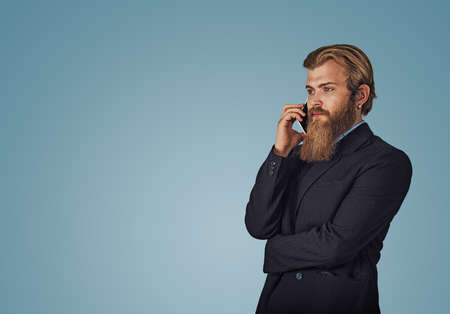 Bearded hipster business man holding talking by mobile phone isolated on blue studio wall Background. Serious face expression, human emotion, body language, attitude. Studio shot. Horizontal shot.