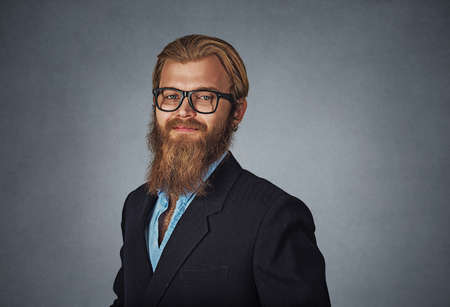 Young handsome Bearded hipster businessman in glasses looking straight at camera smiling Isolated on gray grey studio wall Background. Negative face expression, human emotion, body language, reaction. Banco de Imagens