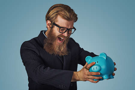 Unhappy man in glasses angry at his piggy bank trying to broke it up, Bearded hipster businessman Isolated on blue Background. Negative face expression, human emotion, body language, reaction attitude