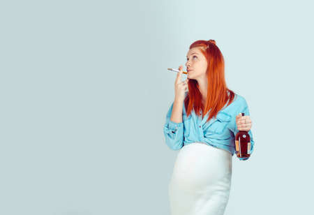 Young careless girl with ginger hair waiting for baby and standing with cigarette and alcohol on light blue background. Mixed race model, latin hispanic irish woman