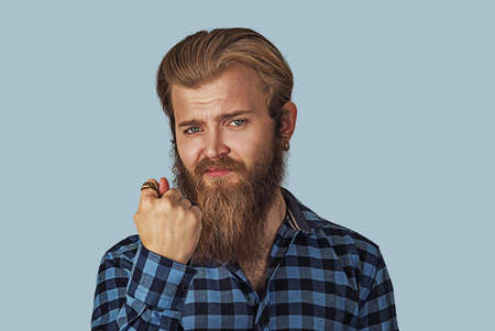 Man giving thumb, finger fig gesture you get zero nothing. Hipster male with beard in blue plaid checkered shirt. Isolated blue studio Background. Negative face expression human emotion body language