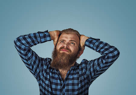 Young desperate man head in his hands clasped. Young frowning male covering ears with hands looking up frustrated with noise from loud upper neighbors. Hipster with beard in blue plaid checkered shirt