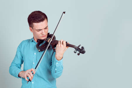 Man in shirt playing modern violin instrument sanding on light background
