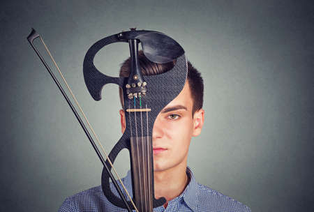 Young man in shirt covering face with violin in modern design looking at camera on gray background