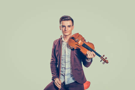 Young handsome man in elegant jacket sitting on chair with classic violin looking at camera