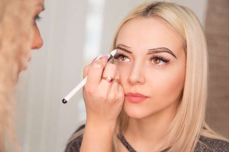 Microblading, micropigmentation eyebrows work flow in a beauty salon. Woman having her eye brows drawn and tinted with black pencil, preparing for semi-permanent makeup for eyebrows. Focus on eyebrow Banco de Imagens