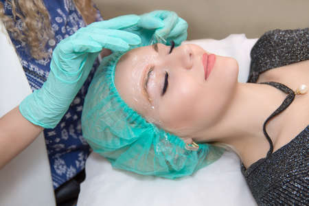 Microblading eyebrows work flow in beauty salon. Technician applying anesthesia on patient brows. Woman having her eye brows tinted Preparations for Semi-permanent makeup for eyebrows Focus on eyebrow Banco de Imagens