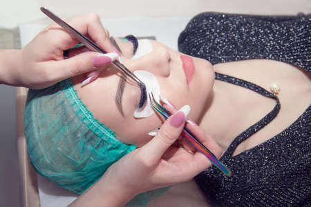 Eyelash extension process. Closeup portrait of young girl, woman with long and thick eyelashes, eyes closed and hand of a cosmetologist with two tweezers tools about to add more eyelashes to her eyes. Banco de Imagens