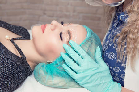 Micro blading eyebrows work flow in a beauty salon. Woman having her eye brows tinted. Preparations for Semi-permanent makeup for eyebrows, anesthesia on brows covered with plastic. Focus on eyebrow