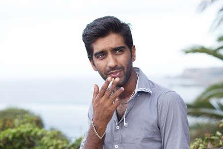 Happy ethnic man smoking cigarette, smiling, thinking looking sidewards outdoors background.