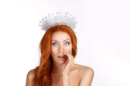 Cheerful happy pretty girl telling secret on white background. Caucasian person beauty queen in crystal crown, with long redhead hair isolated on white studio background