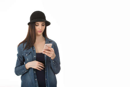 Portrait of beautiful Serious young woman surfing the Internet on cell phone, looking at screen with concentrated expression, checking email, girl wearing casual black hat, blue jeans shirt on white background Banco de Imagens