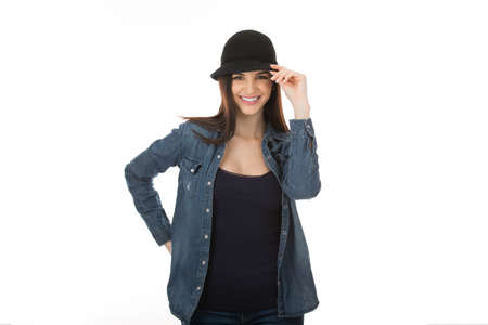 Woman cute girl touching her black hat in sign of salute, greeting someone saying hi with hand gesture isolated on white studio wall background