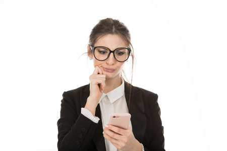 Closeup portrait serious worried displeased businesswoman read bad news on smart phone holding mobile isolated on white background. Negative human face expression, corporate executive emotion Banco de Imagens