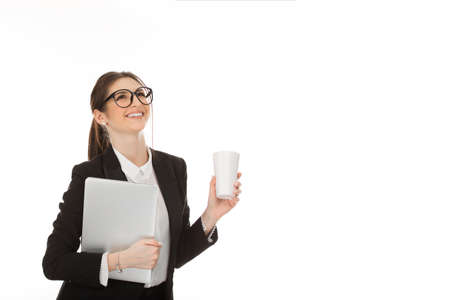 Closeup cutout portrait of a beautiful cheerful woman holding laptop and cup of coffee ready for work laughing happy cheering wearing formal black suit and white shirt isolated on a white background