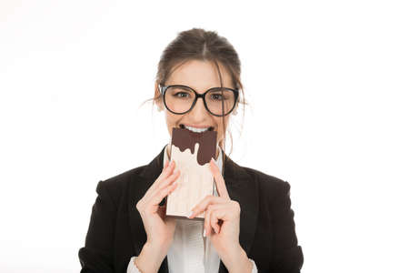 Closeup portrait of a beautiful woman chocolate eating smiling happy looking at camera, excited girl wearing business wear, formal black suit and white shirt cutout isolated on a pure white background