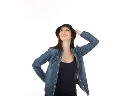 Woman looking up posing smiling, laughing happily, cute hipster girl in black hat posing cheerful isolated on white studio wall background. Positive face expression, human emotion.