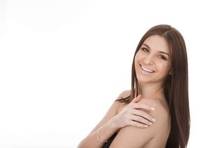 Happy Natural beauty with flawless skin. Brunette model fashion girl posing with hands touching shoulders body showing healthy skin looking smiling to you camera isolated on white background, laughing