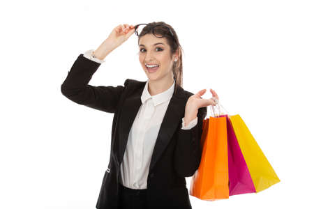 Cutout portrait of a beautiful woman with shopping bags holding her eyeglasses up with euphoric super excited expression on face, girl wearing formal black suit, shirt isolated on white background