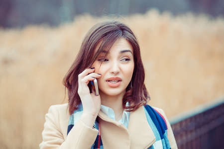 Skeptical woman talking on phone deciding what to answer outdoors on park background Banco de Imagens