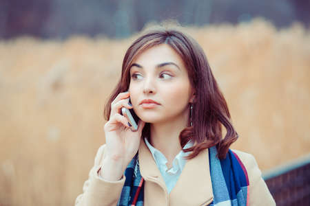 Skeptical woman talking on phone deciding what to answer outdoors park in autumn on background