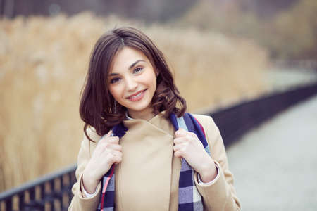 Pretty woman with warm clothes in autumn beige coat looking at you camera city trees, reed thicket park on background. Caucasian model Banco de Imagens