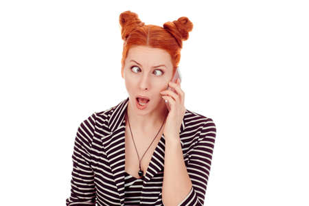 Shocked by phone. Closeup portrait cut out of a beautiful woman in her 30 going crazy while talking at phone shocked crossing eyes in striped black white jacket with 2 buns up hairdo isolated on white