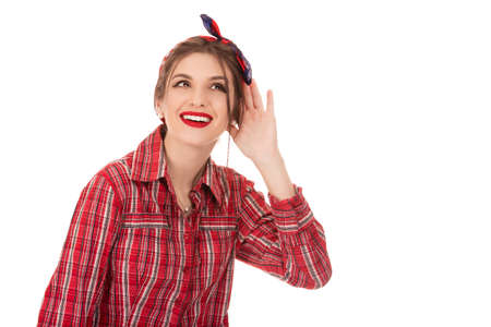 Curious excited woman wearing red checkered shirt and retro bow headband standing with her hand behind her ear and a look of anticipation as she waits to hear a snippet of gossip over white wall