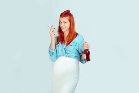 Young careless girl with ginger hair waiting for baby and standing with cigarette and alcohol smiling happy on light blue background. Mixed race model, latin hispanic irish woman