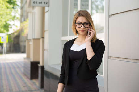 Portrait of unhappy business woman outdoor talking on phone