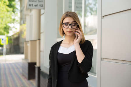 Skeptical at mobile phone. Closeup portrait displeased annoyed doubtful young businesswoman talking with partner on cellphone near office house store background. Negative human face expression emotion Stok Fotoğraf