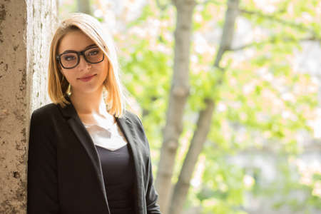 Woman outdoors. Closeup portrait woman girl looking at you camera with serious face with slight smile, black suit formal office wear, eye glasses outside leaning on grunge wall green trees background