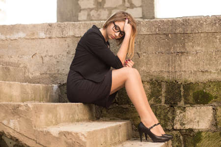 Sad woman sitting on the  stairs of an abandoned building. Upset lonely desperate girl stressed with broken heart in black business clothing formal wear bob hair style hands holding head in despair.