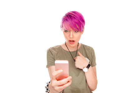 Is it me? you mean me? Pretty young female with pink hair looks at modern smart phone with bugged eyes pointing to herself she received unexpected bad message from friend isolated over white backdrop.