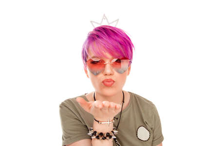 Pleasant looking young female with short pink hair keeps puckered lips puckering as going to blow a kiss to someone has glad expression expresses his love to boyfriend isolated over white background.