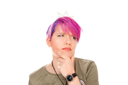Thoughtful. Young woman with pink hair and green eyes frowning her eyebrows hand fingers on chin having doubt and suspicion feeling sceptical about something. Human emotions and expressions concept